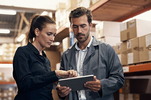 man and woman reviewing tablet in warehouse