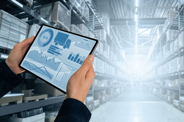 a tablet held in the foreground of a warehouse aisle representing the technical capabilities of tristar's inventory management