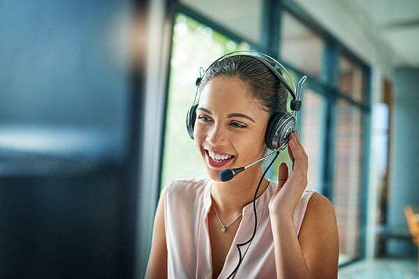tristar customer support representative in modern facility wearing and speaking into a headset